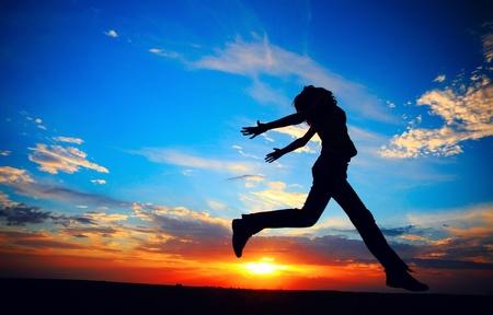 若い女性は、夕日を背景に草原にジャンプします。
