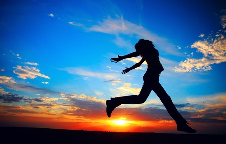 Young woman jumping on meadow on sunset background. Stock Photo