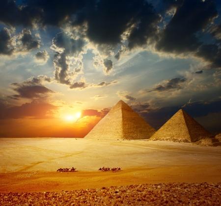 Grattugiare piramidi di Giza in Egitto con la valle del gruppo di beduini su cammelli a cavallo attraverso il deserto Archivio Fotografico - 10676456