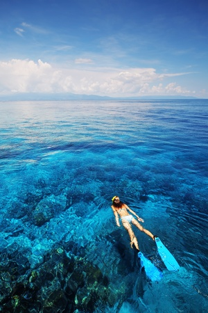 Young woman in swimsuit snorkeling in clear shallow tropical sea over coral reefs photo
