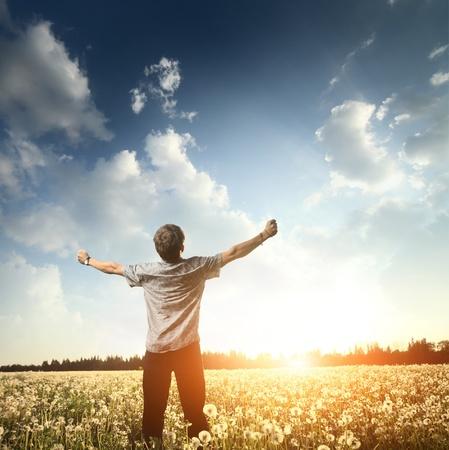 若い男は上げられた手と牧草地に立っていると、空を見ています。 写真素材