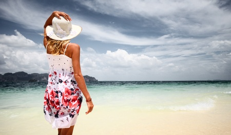 hot climate: Young woman in summer dress standing by sea holding straw hat and looking to the horizon