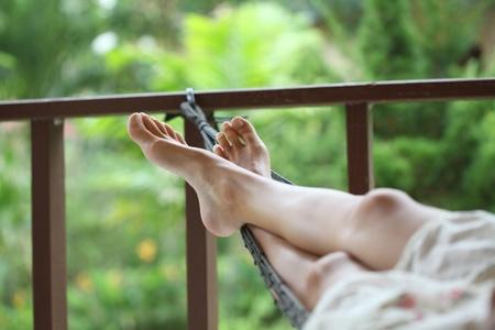 Young woman in summer dress lying in hammock in a garden. Stock Photo - 10675998