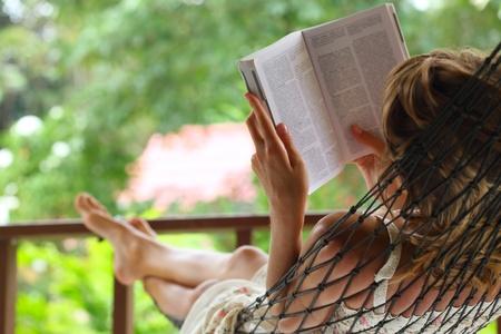 personas leyendo: Joven mujer leyendo un libro en la hamaca en un jardín. Centrarse en la mano izquierda y el hombro Foto de archivo