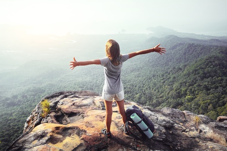 Young woman standing with raised hands with backpack on cliff's edge and looking into a wide valley