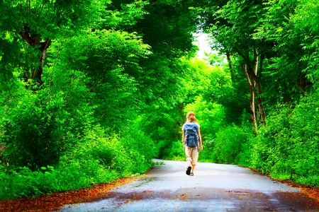 Young woman walking on green asphalt road in forest photo