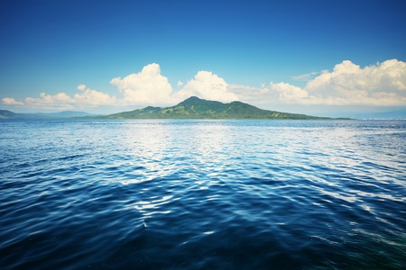 mountain oasis: Blue sea with waves and green island on the horizon Stock Photo