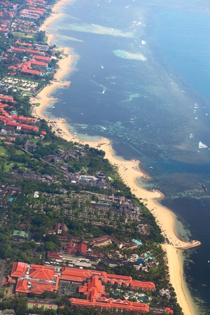 Sandy coast, buildings and blue sea with waves. Bali island view from plane photo