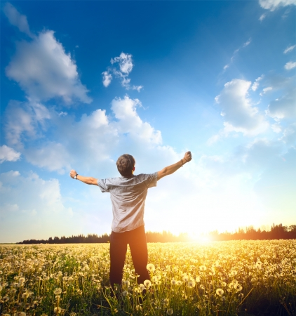 fun in the sun: Young man standing on a meadow with raised hands and looking to a sky