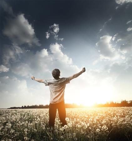 manos levantadas: Joven de pie en un prado con las manos en alto y mirando a un cielo
