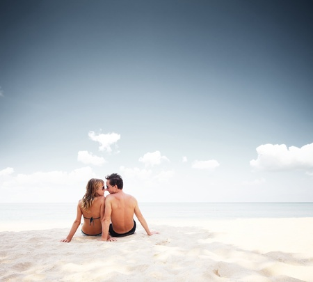 naked woman sitting: Young happy couple sitting on a sand by sea and enjoying each other