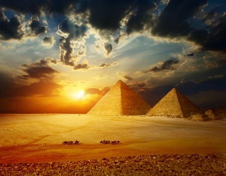 Grattugiare piramidi di Giza in Egitto con la valle del gruppo di beduini su cammelli a cavallo attraverso il deserto