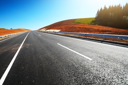 side of light: Empty countryside asphalt road through hills with red soil and clear blue sky Stock Photo