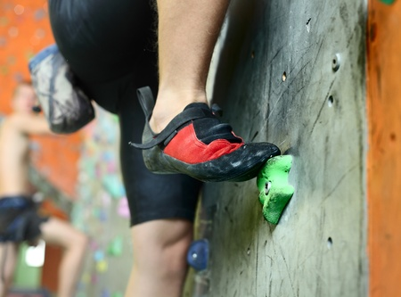 bouldering: Young mans foot climbing indoor wall