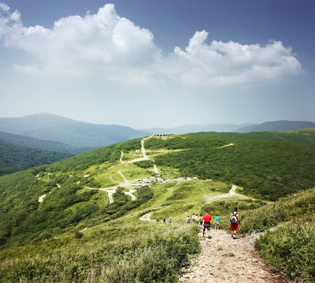 back roads: Group of tourists walking on countryside roads in mountains