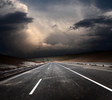 Dirty asphalt road and dark thunder clouds photo