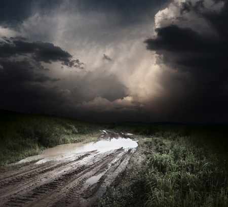 Muddy wet countryside road and dark storm clouds photo