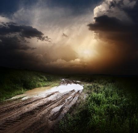 Modderige natte platteland weg en donkere onweerswolken Stockfoto