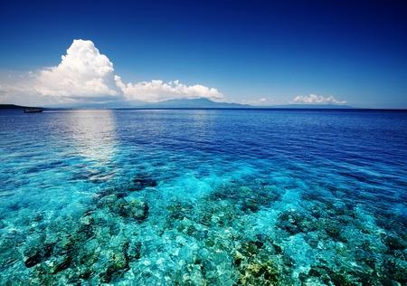 サンゴ礁とふわふわの雲が地平線に青い浅い海 写真素材