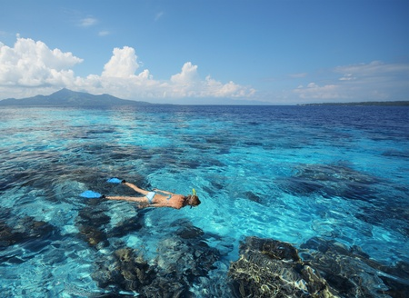 Young woman in swimsuit snorkeling in clear shallow tropical sea over coral reefs