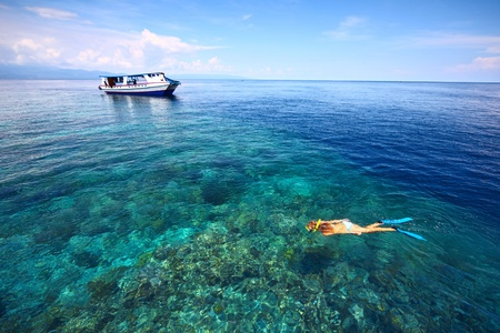 Young woman in swimsuit snorkeling in blue and transparent tropical sea not far away from a boat photo