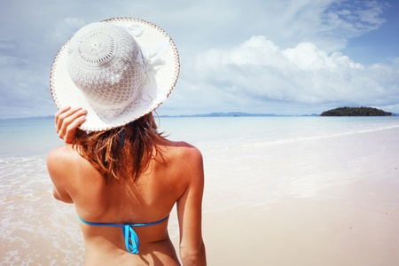 Young woman standing on a beach holding her straw hat and looking to the horizon. photo