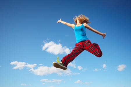 vitality: Young happy woman jumping on blue sky background