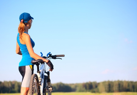 space weather tire: Young slender woman standing by bicycle and looking to a sky