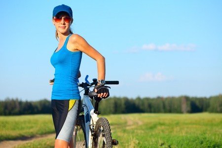 slender woman: Young slender woman in red glasses standing by bicycle and looking to a camera