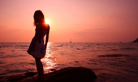 Young woman in summer dress standing on a rock and looking to a sea photo