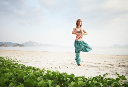 standing water: Young woman doing yoga exercises and relaxing on a sand Stock Photo