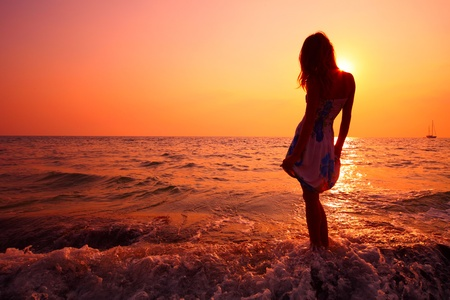 splash back: Young woman in summer dress standing on a rock and looking to a sea
