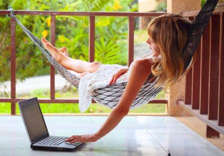 Jonge vrouw liggend in een hangmat in de tuin en op zoek naar een laptop Stockfoto