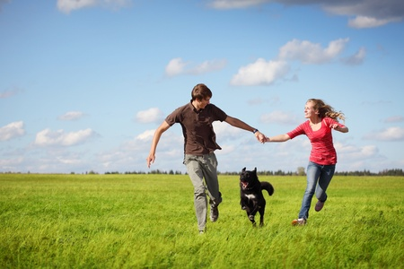 woman with dog: Feliz pareja de j�venes corriendo en un prado verde con un perro negro