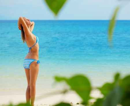 hot climate: Young woman standing on a sand and relaxing