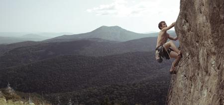 若い男が山と谷の岩壁の上に登る 写真素材