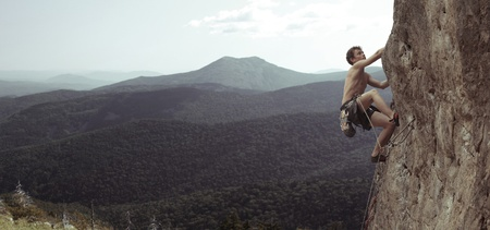 mászó: Fiatal ember felmászik egy sziklás fal egy völgyben, a hegyek