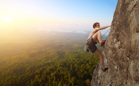 tenacity: Young man climbs on a rocky wall in a valley with mountains at sunrise