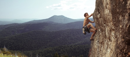 free climbing: Young man climbs on a rocky wall in a valley with mountains