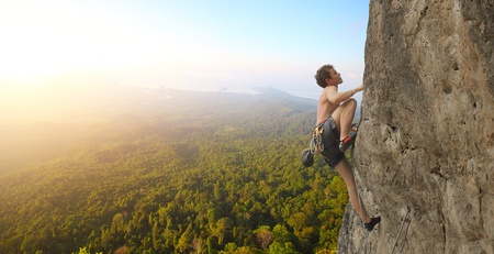 Young man climbs on a rocky wall in a valley with mountains at sunrise Stock Photo - 11149698
