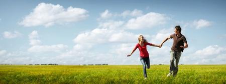 Feliz pareja de jóvenes que se ejecutan en un prado verde con cielo nublado azul en el fondo Foto de archivo - 11149554