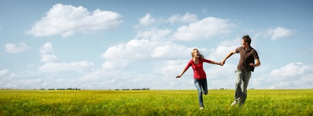 Junges Paar glücklich läuft auf einer grünen Wiese mit blauem Himmel bewölkt auf dem Hintergrund Standard-Bild