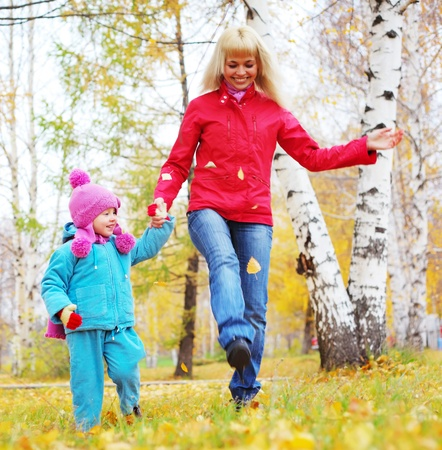 Happy young mother and her little daughter walking in an autumn park photo
