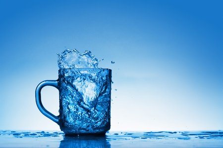 Glass and water splashes on blue background photo