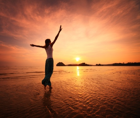 manos levantadas: Joven mujer caminando en una playa de arena