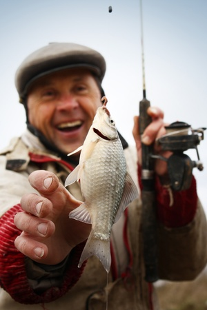 Happy smiling fisherman with fresh caught crucian (Carassius of family Cyprinidae) on clear sky background Stock Photo - 11149543