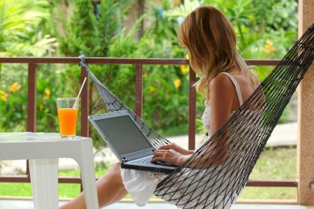 hamaca: Joven mujer sentada en una hamaca en un jardín y escribiendo algo en un ordenador portátil Foto de archivo