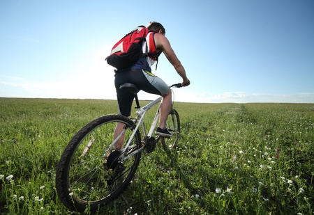 dynamic activity: Young man riding on bycycle through deep grass with red backpack