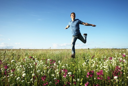 at ease: Young man running on meadow with pink flowers and green grass on a blue sky  Stock Photo