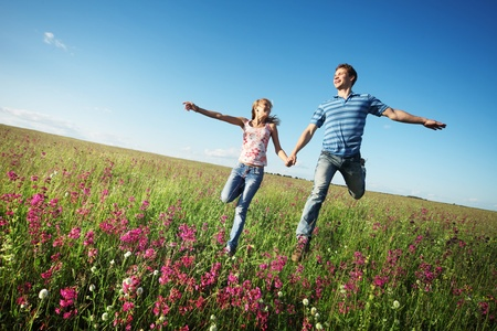 Young happy lovers running on meadow with green grass and pink flowers on a blue sky photo